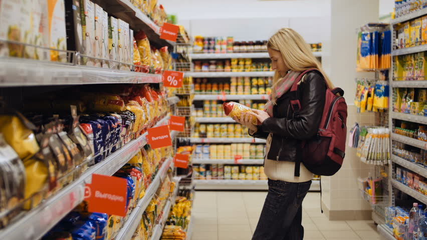 Blond lady pick pasta from shelf, examine it and put back