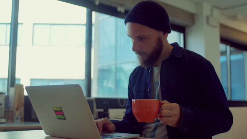 Man drinks coffee while working in the startup office