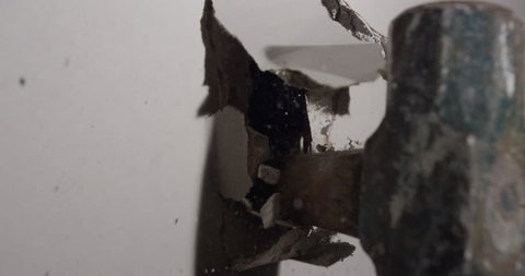 Slow motion hammer smashing through drywall in house renovations