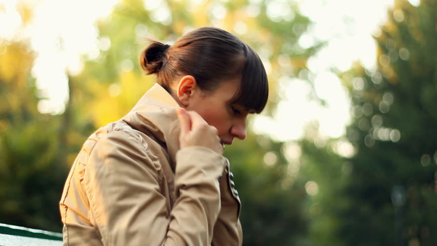 Sick woman sitting on park bench and coughing