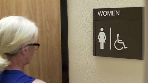 woman walking into an office womans restroom 4k