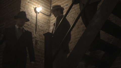 NEW YORK CITY - SEPTEMBER 2013.  Re-enactment, recreation of 1920s, 1930s Gangster/Mobster in Dark Hallway, walk down staircase together.  Mobster, mob boss during prohibition days. Boardwalk Empire.
