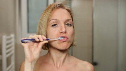 Woman brushing her teeth in front of bathroom mirror.