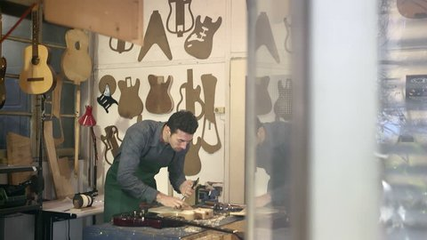 People at work, art, man working as artisan in Italian workshop with guitars and musical instruments