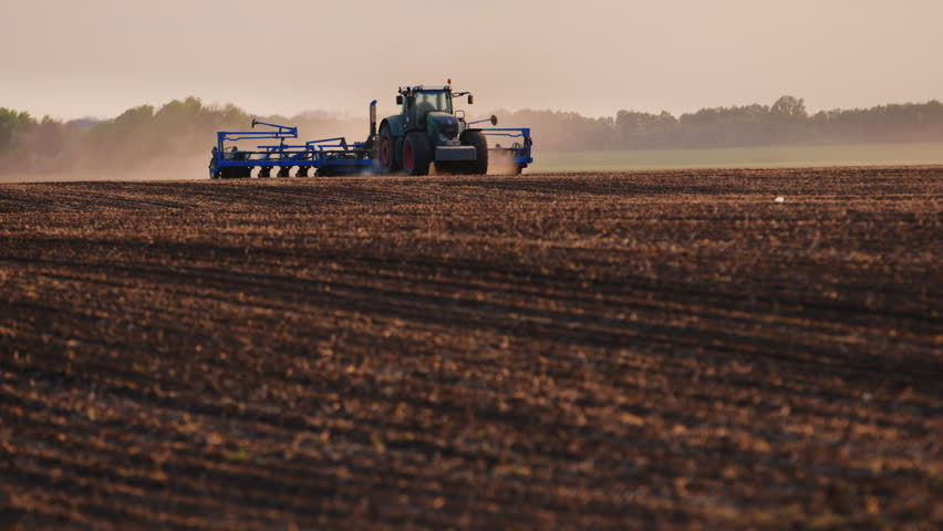 Tractor with drill goes through the field, carried out in spring seeding   Shutterstock HD Video #16413190