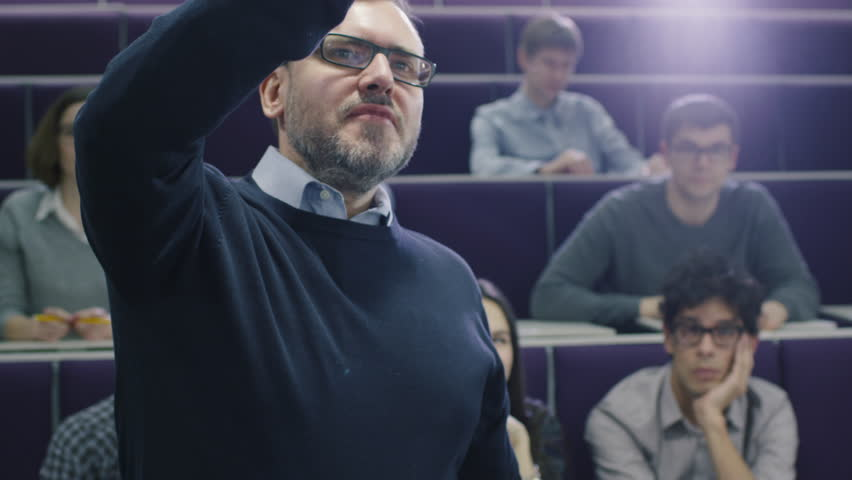 College professor is teaching a class of multi-ethnic students while pointing the desk with a marker. Shot on RED Cinema Camera.