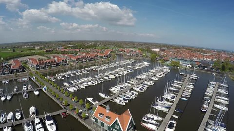 Aerial flying over  the recreational harbor of Volendam showing recreational boats ships harbor town is popular tourist attraction in Netherlands known for old fishing boats traditional clothing 4k