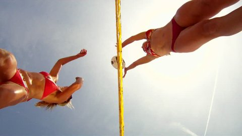 POV looking up of two women spiking and blocking beach volleyball at the net. - Model Released - 1920x1080 - Full HD