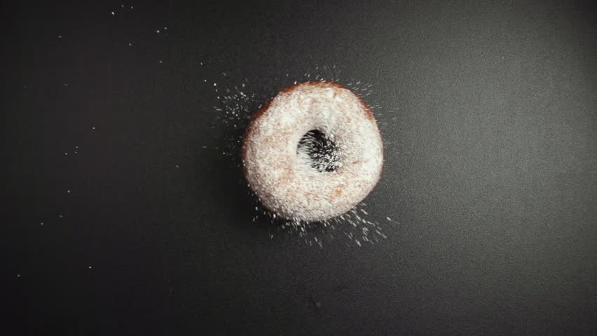 SLOW: A donut falls on a black table and turn (top view)