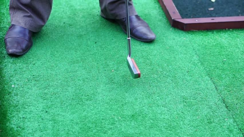 Takes aim at the ball, mini Golf | Shutterstock HD Video #16584010