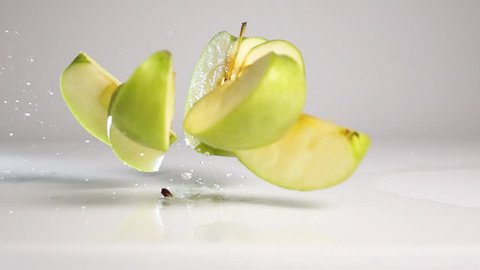 Fresh tasty green apple falling down and breaking up into pieces and rolling onto it sides on wet white floor with stunning explosive splash. Shoot with high speed camera in slow motion mode. White