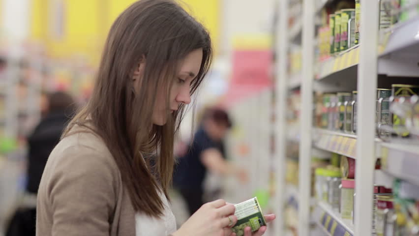 Young woman chooses canned food in the store | Shutterstock HD Video #16614082