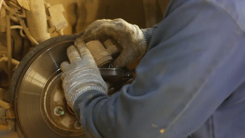 A car mechanic repairing a vehicle break, 4k uhd 2160p