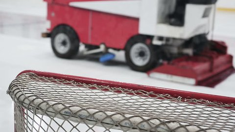 Close-up of hockey net, ice resurfacer driving rink to make surface smooth