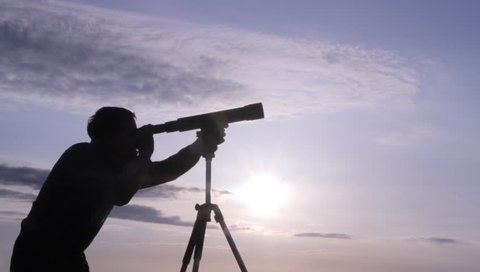 silhouette of a man watching through a telescope