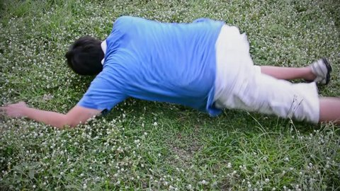 An Asian Thai man guy drop dead on the grassy ground field in HD