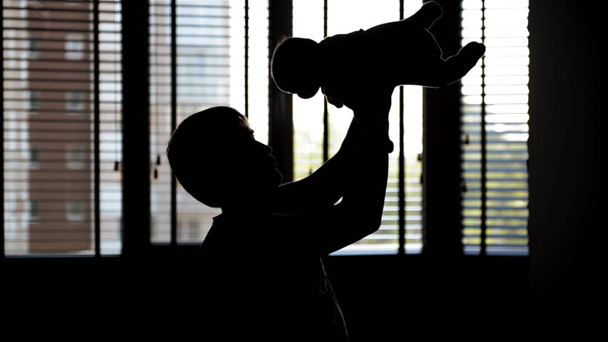 Young father with his little baby playing, shadow. Father's day