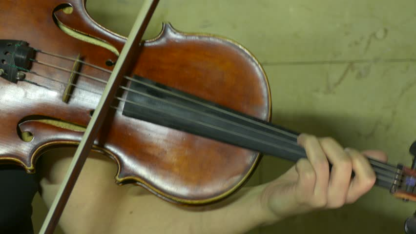 Ungraded: Violinist playing / Violin Player / Orchestra Musician. Female violinist plays violin at a classical music concert. Violin close-up. Source: Lumix DMC, ungraded H.264 from camera. (av24823u)