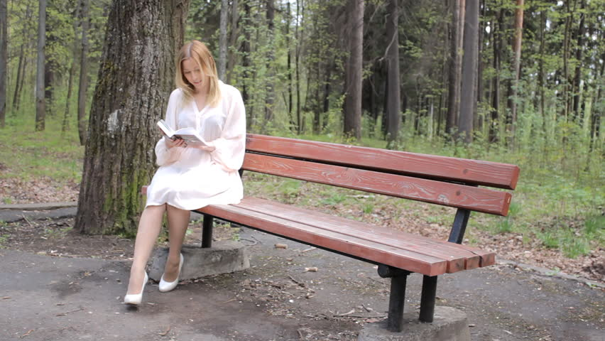 Nice Video Bench Part - 5: Girl Sits On A Bench With A Book. Young Woman Reading A Book And Sitting