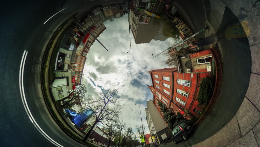 People Walk by City Street Among Buildings, Red Bricks Houses, vr Video 360, Little Planet Video, Video For Virtual Reality, Time Lapse, Road Markings, Cars Moving by Paved Road, White Clouds,