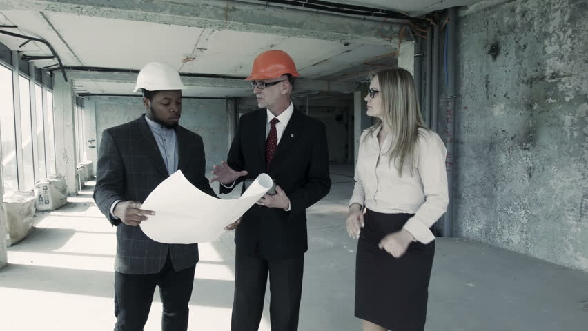 Young african american manager of the construction company goes men woman in suit and helmet discuss blueprint communicate with buyer chief engineer malvernweather Images