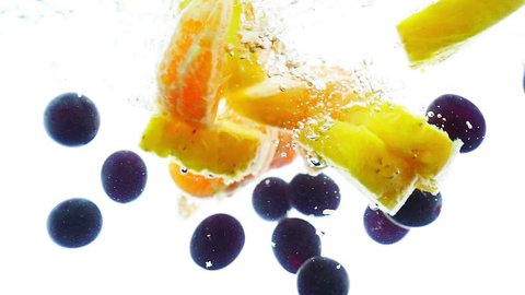 Mixed fruits falling into water in slow motion. Pineapple, tangerine and grapes. Slow-motion.