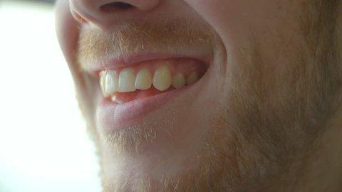 Close up of man's mouth opening to smile, closing, side view