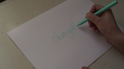4K girl writing OMG ohmigod, oh my god, on white paper in slang with felt pen. A teenage British girl is writing slang ohmigod, OMG, oh my god, on a white paper using a blue felt pen, on a white wood