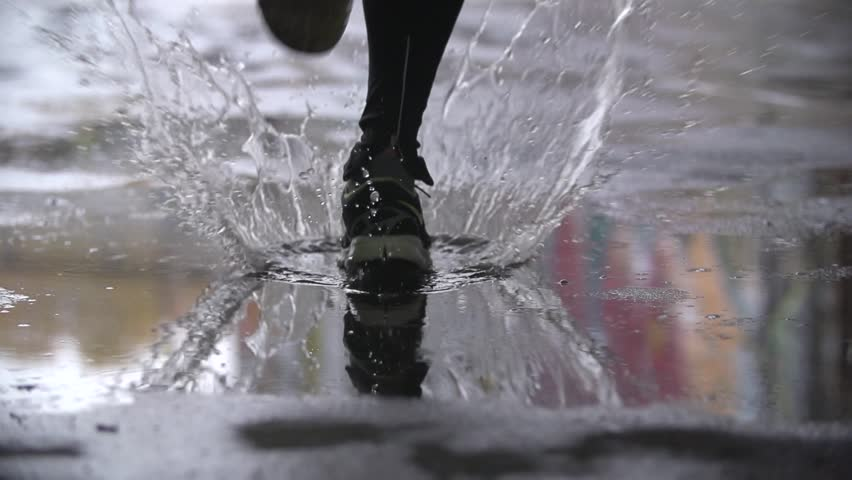Close up slow motion shot of legs of a runner in sneakers. Male sports man jogging outdoors in a park, stepping into muddy puddle. Single runner running in rain, making splash. #16808320