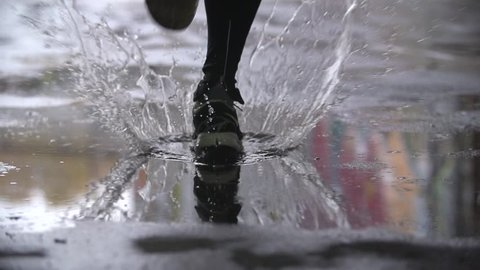 Close up slow motion shot of legs of a runner in sneakers. Male sports man jogging outdoors in a park, stepping into muddy puddle. Single runner running in rain, making splash.
