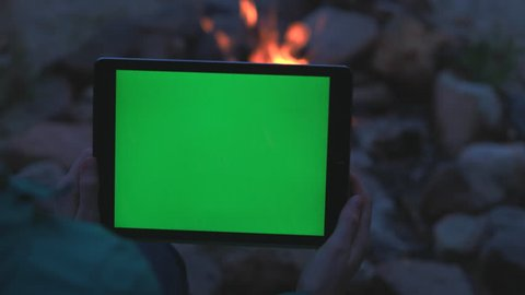 Female Holding Tablet by a Camp Fire with Green Screen.