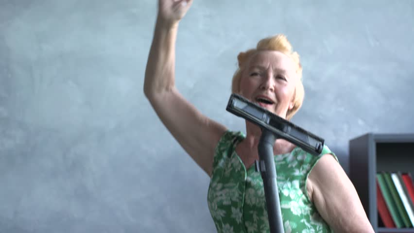 happy elderly woman dancing with a vacuum cleaner, home fun