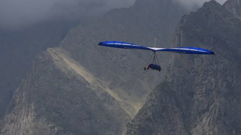 Blue hangglider is trying to gain altitude in a dynamic upward flow near the rocks
