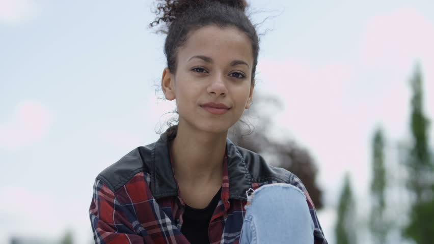 Portrait of a young african american woman wearing checkered shirt, outdoors. Portrait of a young black woman with afro hairstyle in urban background