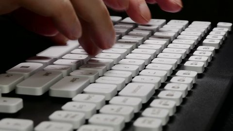 Ungraded: Hands on Keyboard / Typing on Computer / Keyboard Keys. User types a text using english keyboard against black background. Source: Lumix DMC, ungraded H.264 from camera. (av27613u)
