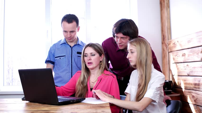 Two pairs of people in the team working with a laptop in business center | Shutterstock HD Video #16873099