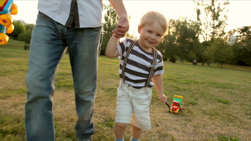 father and little boy running with toy car (slow motion)