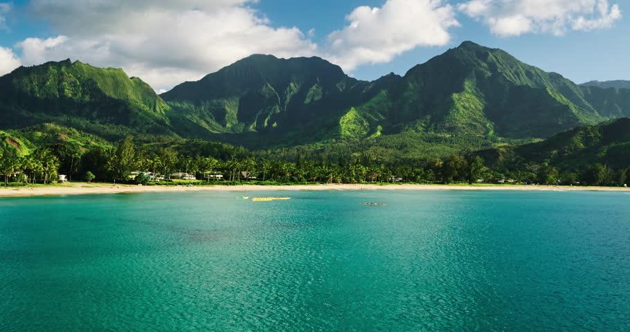 Aerial view flying over hawaiian canoes towards beautiful green mountains and white sandy beach. Hanalei Bay, Kauai   Shutterstock HD Video #16907254