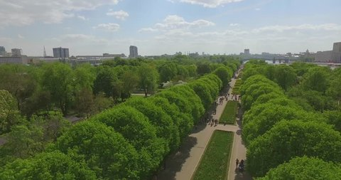 Aerial view of green trees in the park, cityscape, flowerbeds, crowds of people walking on the sidewalks, river bank, Moscow river on sunny summer day. Gorky park, Moscow, Russia.