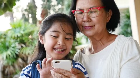 Little Asian girl using smart phone with her grandmother, Happy family concept, Slow motion with pan shot.