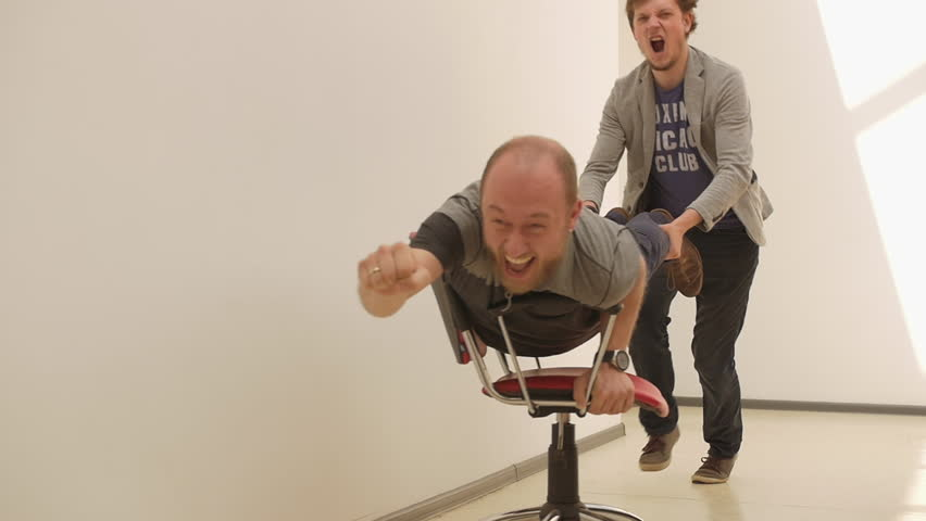Office chair race. Young guys have fun in the office during a break. Games of businessmen from large offices. Men celebrate a successful deal like superhero. Office business party. Slow motion.