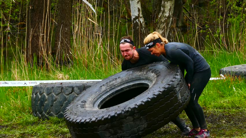 STOCKHOLM, SWEDEN, MAY 2016: Obstacle course racing-Tough viking 14 may 2016 in Stockholm Stadion- Men and women participants helping each other to turn over tractor tires