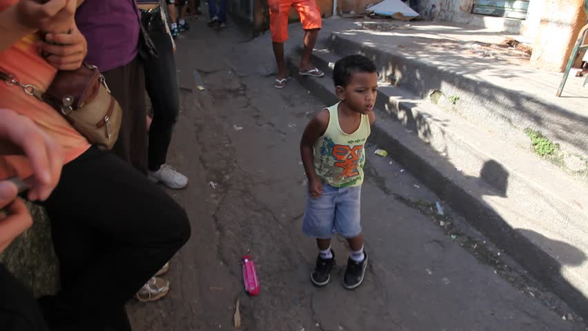 SAN PAULO, BRAZIL - CIRCA JUNE 2011: Brazilian kids play makeshift drums as a young kid dances in the street circa June 2011 in San Paulo.