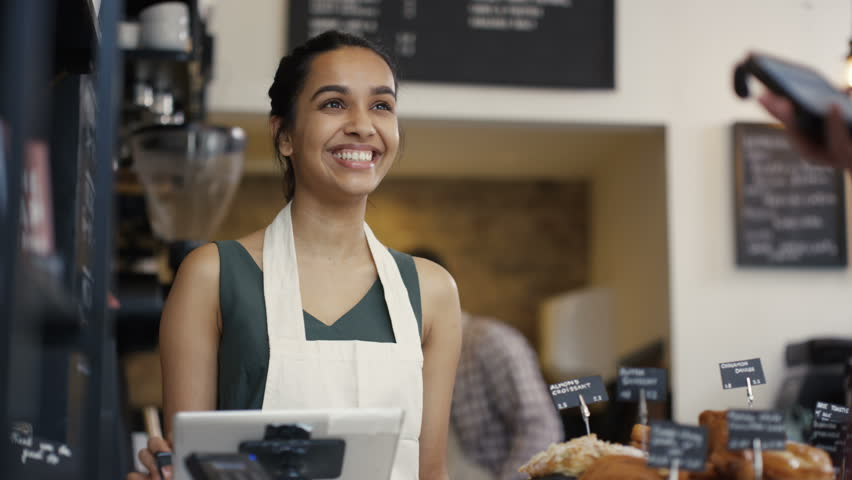 4K Cheerful worker serving a customer who uses smartphone to pay in coffee shop. UK - April, 2016 | Shutterstock Video #16996150