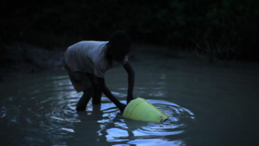 KENYA, AFRICA - CIRCA AUGUST 2010: Boy uses bucket to collect water from water hole at night in Africa circa August 2010.