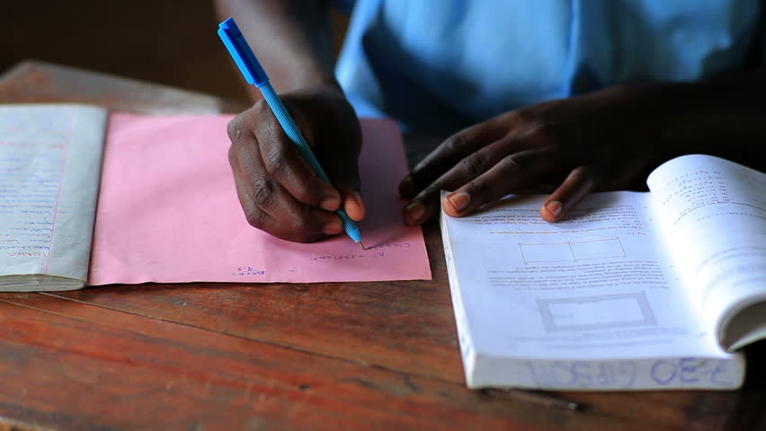 Close up on hands of school boy doing homework after school in Kenya, Africa.