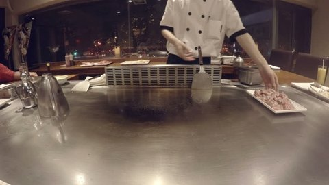 Japanese chef prepares beef teppanyaki on hibachi. Seafood prawns and scallops fried on hot plate by master chef, sizzling and steaming on oily surface.