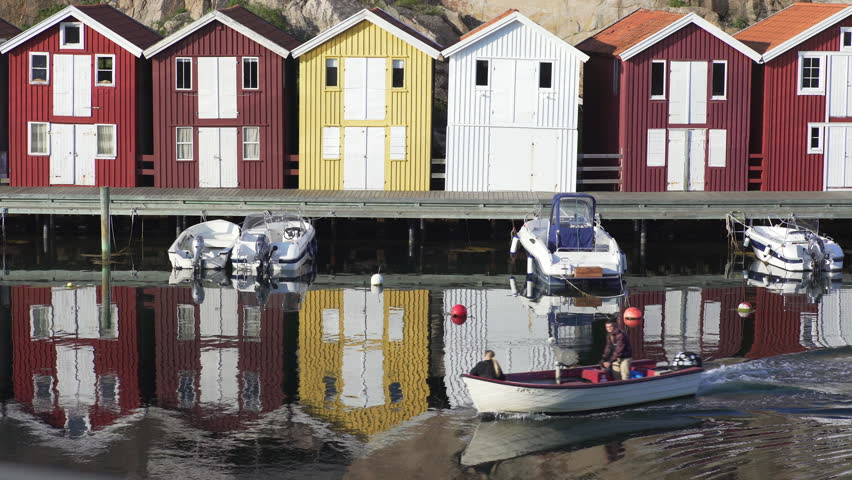 Smogen, Sweden - May 27, 2016: Boat passing by in a canal on the Swedish West Coast (district Bohuslan). In the background, typical Swedish boathouses.