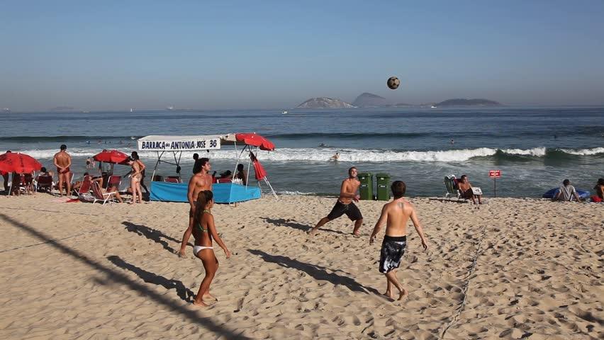 RIO DE JANEIRO, BRAZIL - CIRCA JUNE 2011: Young adults kick around a ball on Copacabana Beach circa June 2011 in Rio de Janeiro.