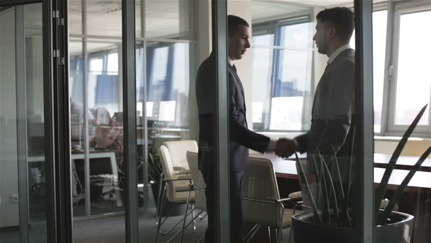 Two businessmen meet and shake hands in a meeting room. Business people is sitting down to a round table and talking.